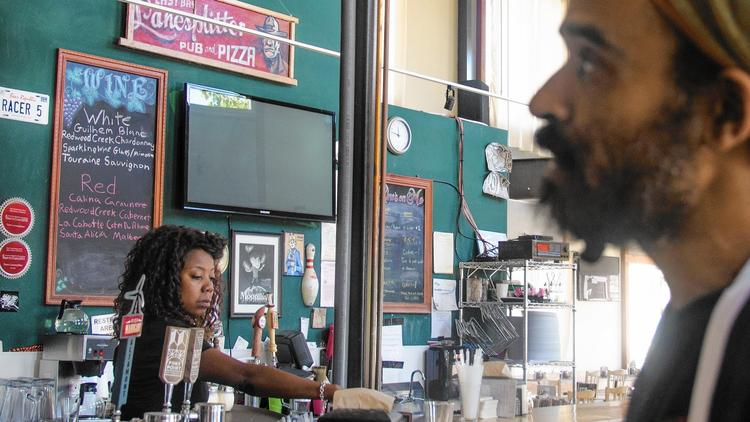 "Nina Gates, 44, and Ira Gibson, 39, are employees of Lanesplitter Pizza & Pub in Emeryville, Calif., whose workers earn $15 to $25 an hour as part of a business model that also did away with gratuities and raised prices, making meals at all five locations ""sustainably served … no tips necessary."" (Lee Romney / Los Angeles Times)"